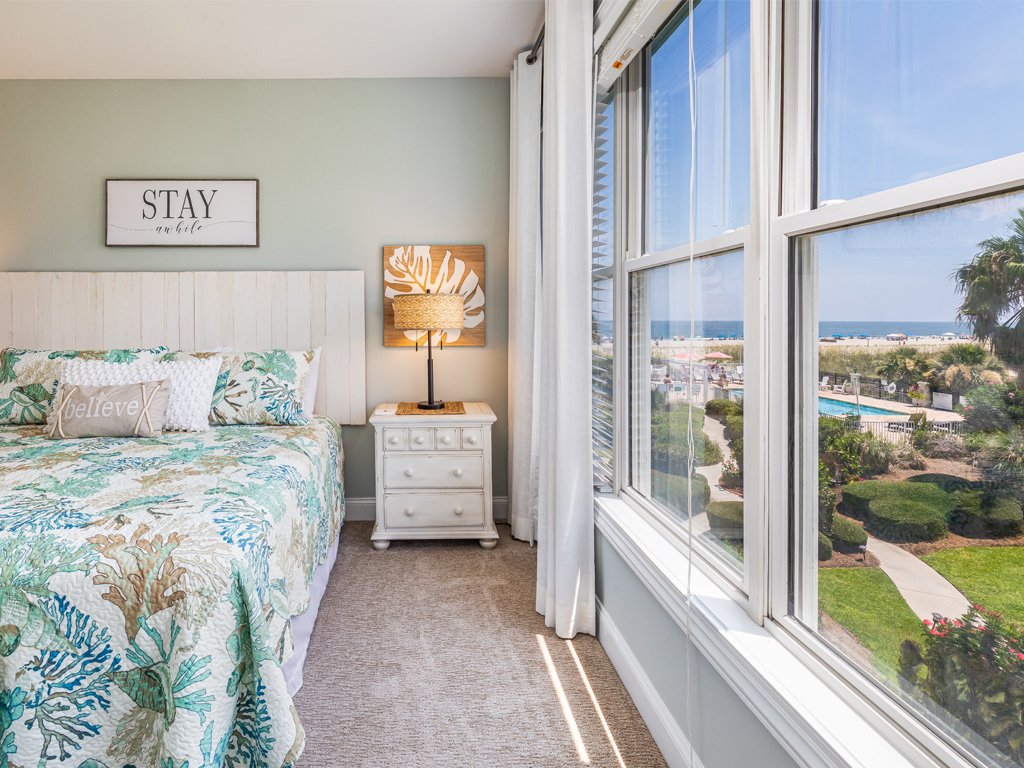 Bedroom with views out the window of a pool, ocean and sunrise.