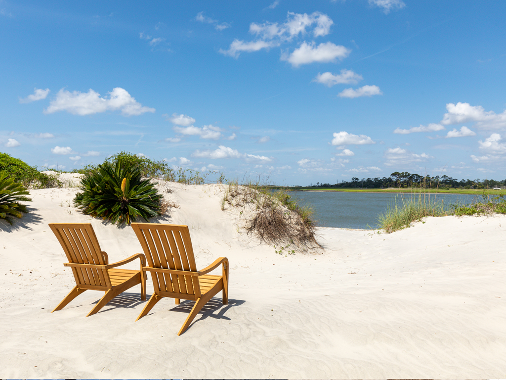 Wooden adirondack chairs in the sand facing the beach