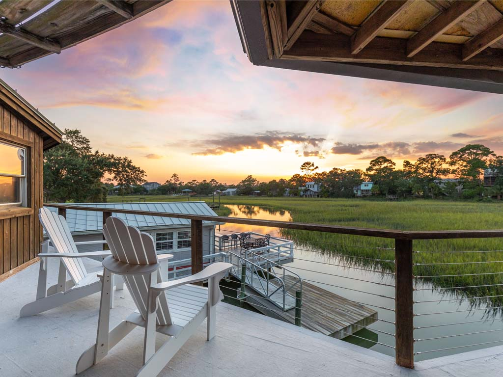 Two chairs on a partially covered open deck with view of the sun setting over the creek and marsh