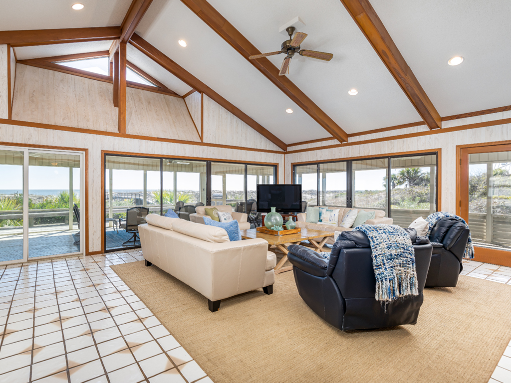 Large open living area with large windows showing a wrap around porch and ocean views