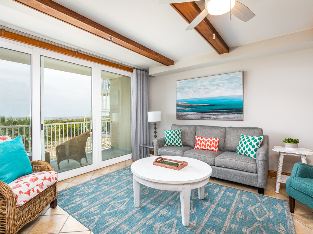 Living room of an oceanfront condo with views of the beach and sunrise