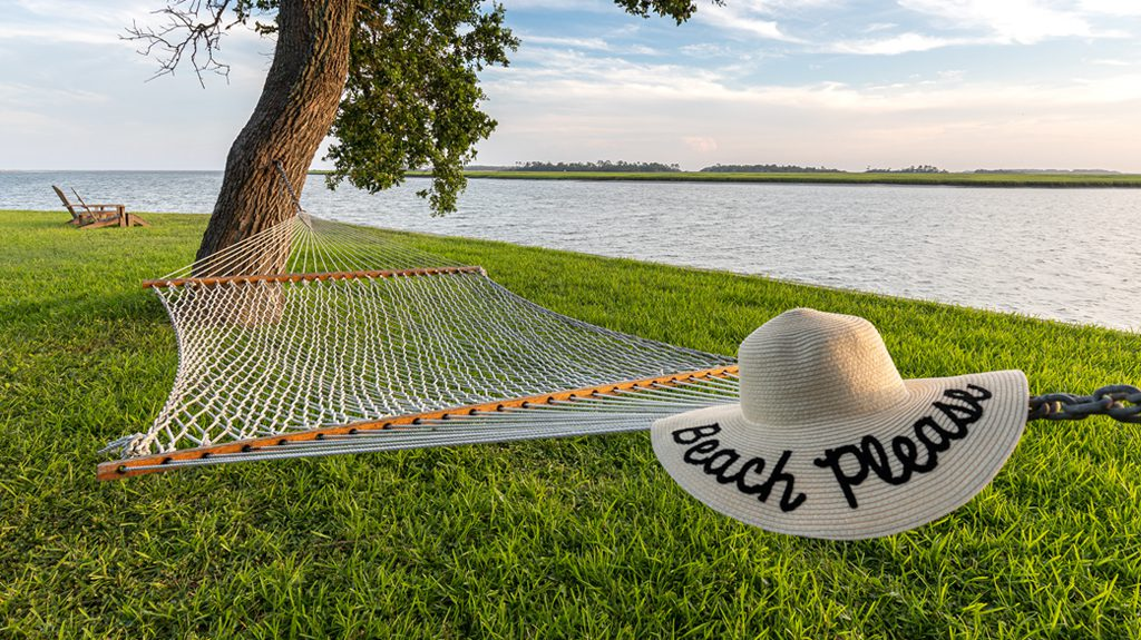A floppy beach hat on a hammock stretched between two trees overlooking the water