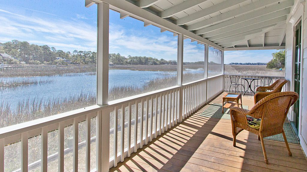 Screened porch with wicker chairs and table looking out towards the water and marsh