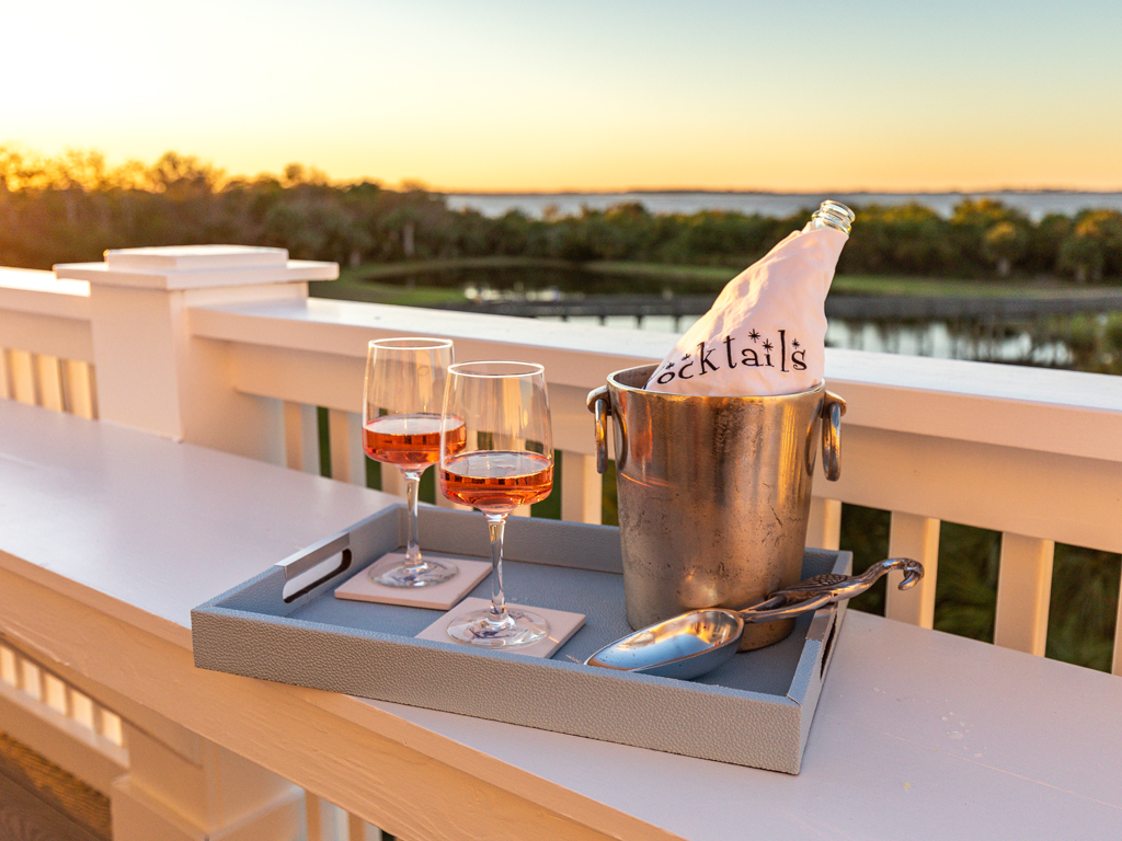 Beverage tray with bottle of champagne and wine glasses with views of the sunset in the background